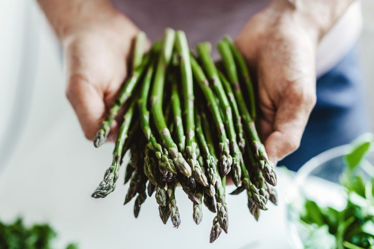 Clean eating or vegetarian concept. Young man holding fresh bundle of asparagus in the kitchen. Closeup.
